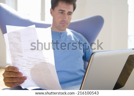 Man with paperwork in armchair, low angle view
