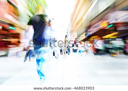 Man with phone. Diversified young crowd on street. Zoom and motion blurred.