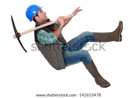 Man with pick-axe falling - stock photo