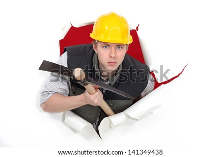 Man with pick-axe tearing through poster - stock photo