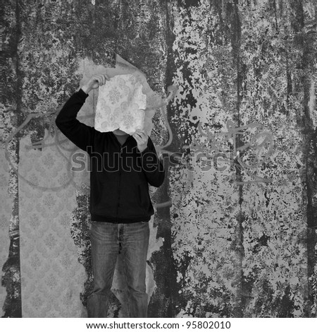 Man with piece of torn wallpaper in decayed room. Black and white.