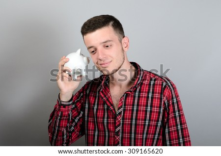 Man with Piggy moneybox Isolated On Grey Background - stock photo