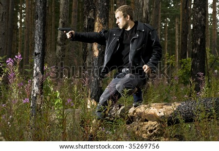 man with pistol in the forest - stock photo