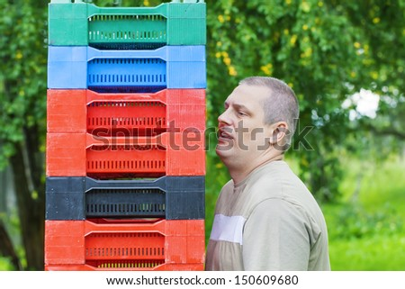 Man with plastic boxes in the garden near fruit trees - stock photo