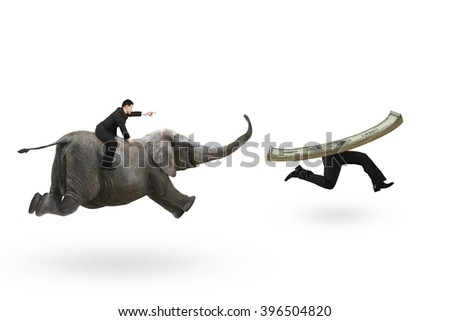 Man with pointing finger gesture riding elephant and running after money with human legs, isolated on white background. - stock photo