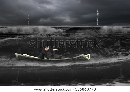 Man with pointing finger gesture sitting on money boat in dark stormy sea with wave coming. - stock photo