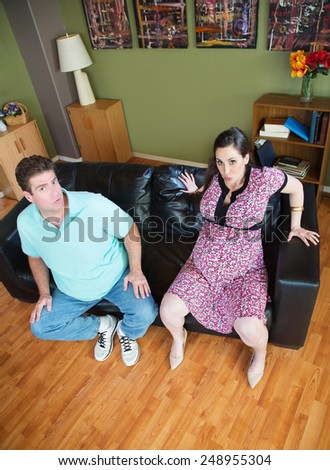 Man with pregnant woman stuck in sofa - stock photo