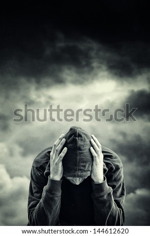 Man with problems. Man in hood with hands on his head. Drug addict concept. - stock photo