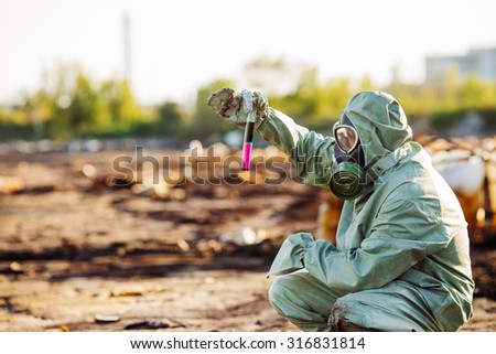 Man with protective mask and protective clothes explores danger area