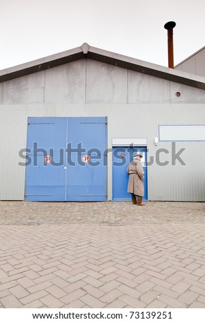 Man with raincoat and hat standing in front of closed door of industrial building.