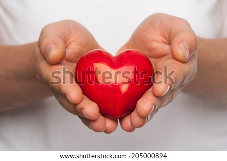 Man with red heart in his hands over body background.
