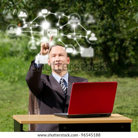 Man with red laptop in social networks outdoors, push the button