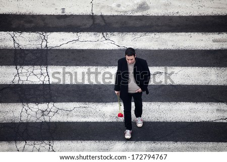 Man with red roses crossing the street