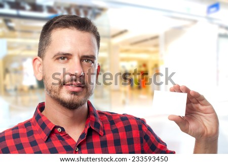 Man with red shirt over shopping center background. He is showing a white card