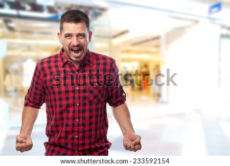 Man with red shirt over shopping center background. Looking upset - stock photo