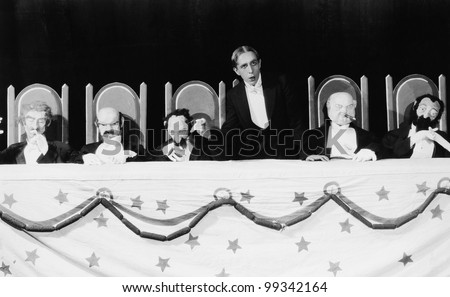 Man with row of seated puppets - stock photo