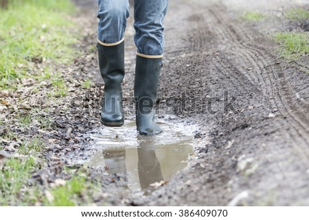 Man with rubber boots walking on rural path