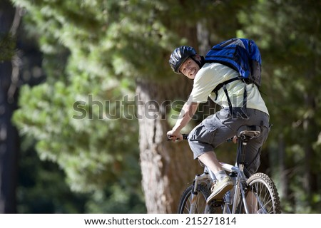 Man, with rucksack and cycling helmet, mountain biking on woodland trail, smiling, rear view - stock photo