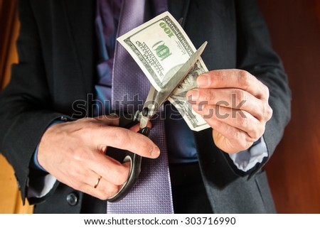 Man with scissors cuts the banknote denominations of 100 dollars( hundred dollar bill) - stock photo