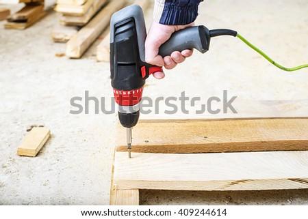 Man with screw gun or screwdriver, Building master, carpenter working  with drilling machine, repairing, repair - stock photo
