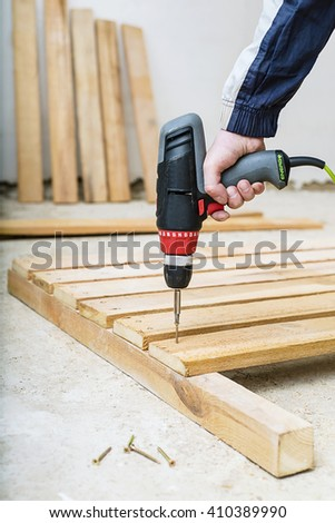 Man with screw gun or screwdriver, Building master, carpenter working   with drilling machine,  carpenter working ,  screw in the board - stock photo