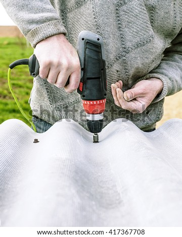 Man with screw gun or screwdriver, repair of the roof of slate,  Building master, carpenter working   with drilling machine,  carpenter working ,  screw in the board - stock photo