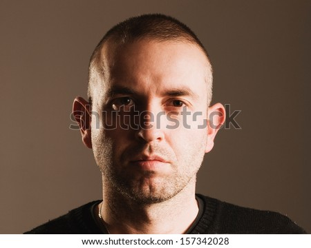 Man with seriously expression, looking and camera and isolated over dark background - stock photo