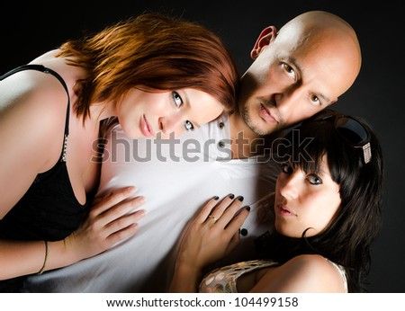 Man with shaved head and two beautiful girls adoring him - stock photo