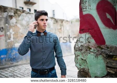 Man with shirt and jeans talking by phone and walking down the street - stock photo