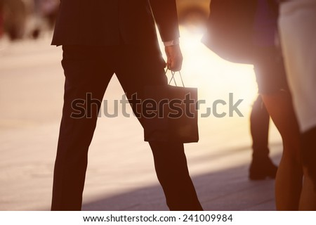 Man with shopping bag on sunny shopping street - stock photo