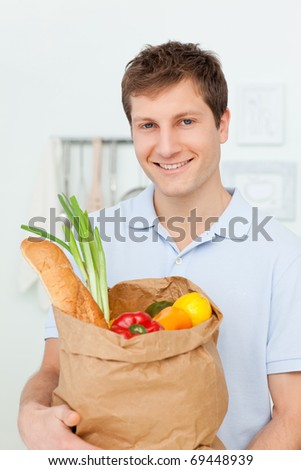 Man with shopping bags in the kitchen at home - stock photo