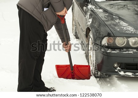 Man with shovel clears snow  around the car - stock photo