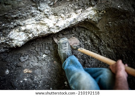 man with shovel working at a hole in the ground - stock photo