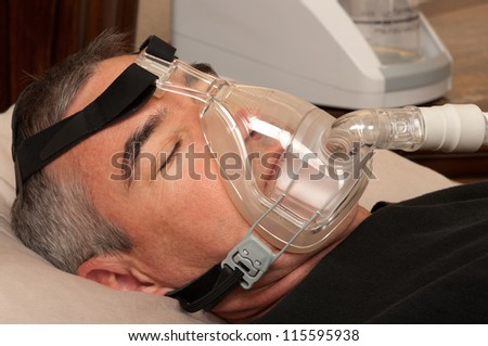 Man with sleeping apnea and CPAP machine - stock photo