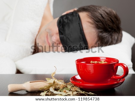 Man with Sleeping mask sleep on a bed, cup of herbal tea in the foreground. Focus on tea cup - stock photo