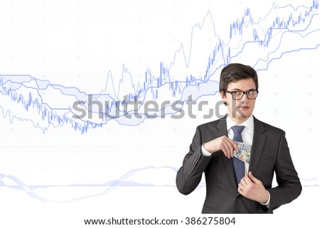 Man with sly look putting one hundred dollar banknotes into the chest pocket. Blue graphs at white background. Concept of getting rich. - stock photo