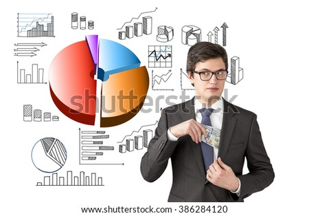 Man with sly look putting one hundred dollar banknotes into the chest pocket. Pie diagram and graphs at background. Concept of getting rich. - stock photo