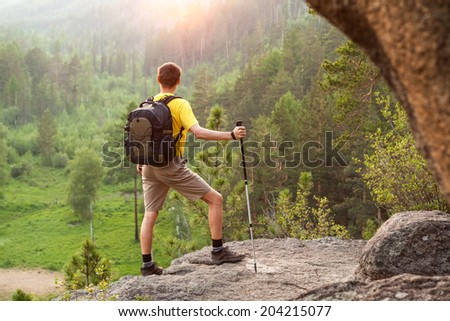 Man with small backpack go up mountain and looking at sunrise
