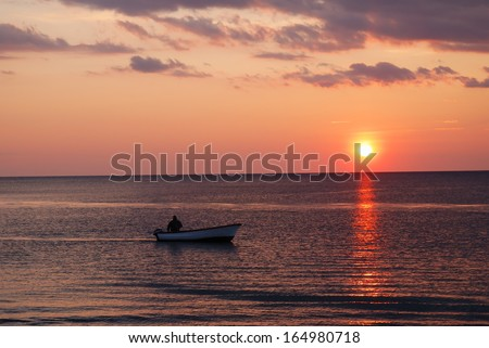 man with small motor boat in the sea at sunset
