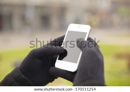 Man with smart phone in hand, glove, blurred background - stock photo