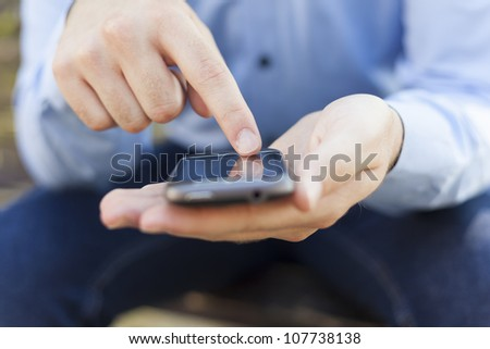 Man with smart phone on hand, blurred background