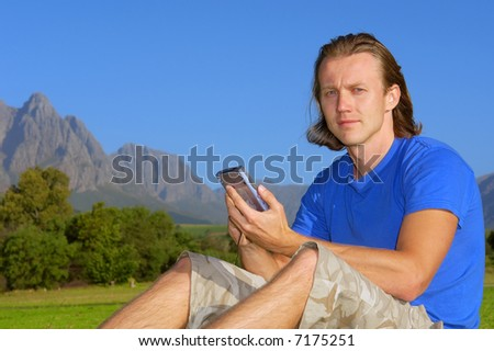 Man with smartphone/pda/gps looks in camera - and misty mountains are background. Shot in Stellenbosch, South Africa.