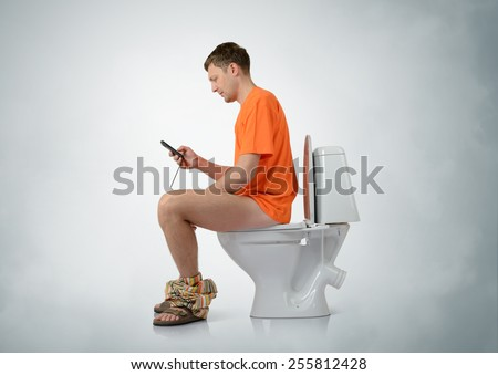 Man with smartphone sitting on the toilet - stock photo