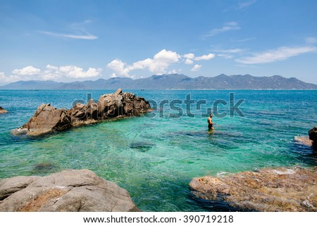 man with snorkel in turquoise sea lagoon in Vietnam