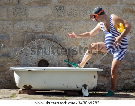 Man with snorkeling gear going to the bathtub outdoor. Funny man in a retro swimsuit goes to a tub with an inflatable toy - duck. Man with diving goggles step to bathtub. Bath a childish man.