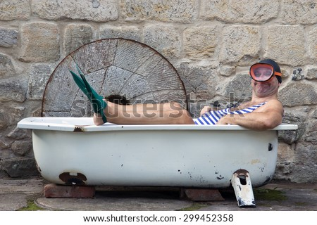 Man with snorkeling gear lying in the bathtub outside - stock photo