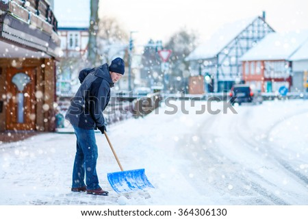 Man with snow shovel cleans sidewalks in winter. Winter time in Europe. Young man in warm winter clothes - stock photo