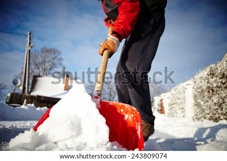 Man with snow shovel cleans sidewalks in winter. Winter time. Latvia. Europe.