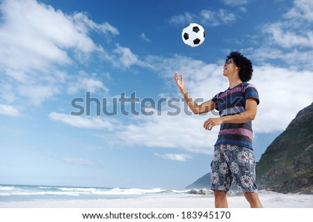 Man with soccer ball on beach and sunglasses