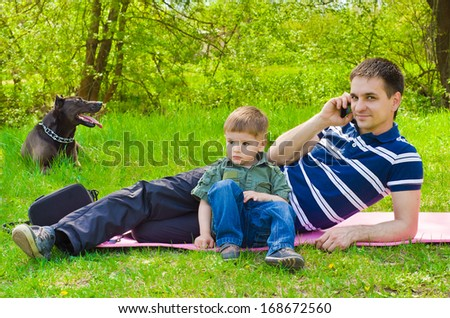 Man  with son and dog outdoors talking on the phone - stock photo